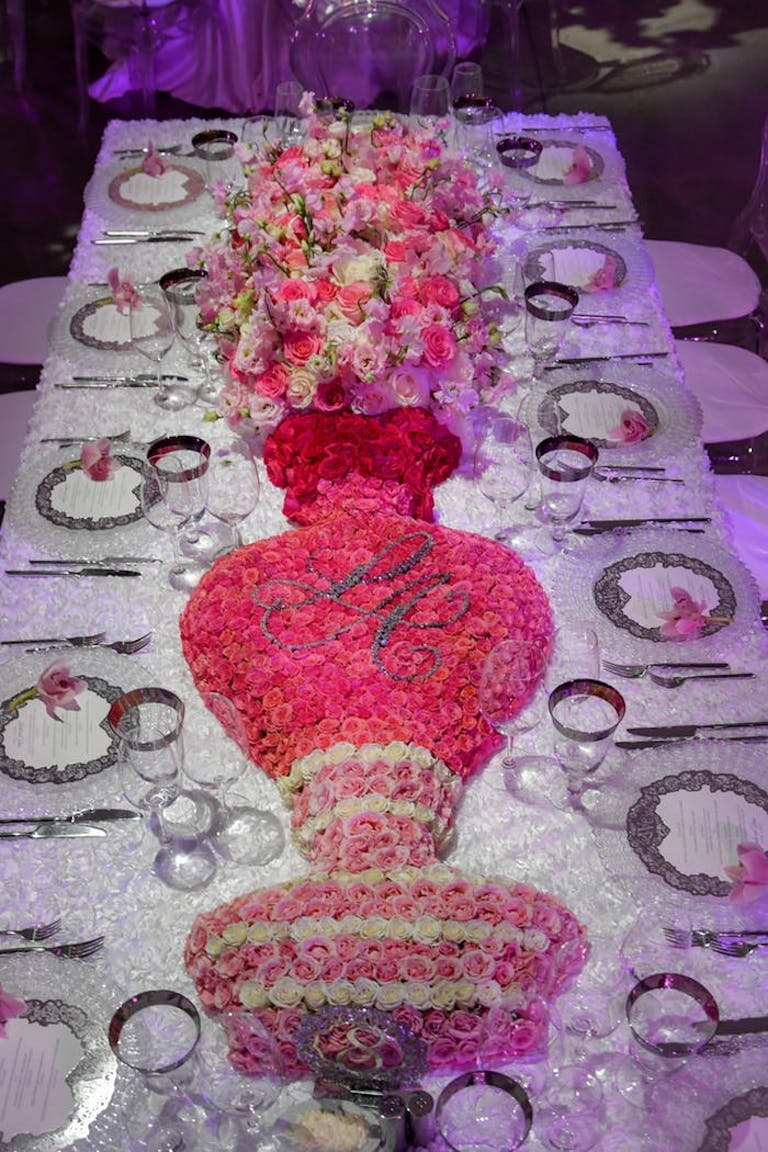 Centerpiece made of flowers in the shape of a vase and pink and white florals coming out the top