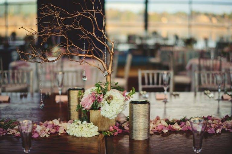twiggy centerpieces with flower petals between each bouquet