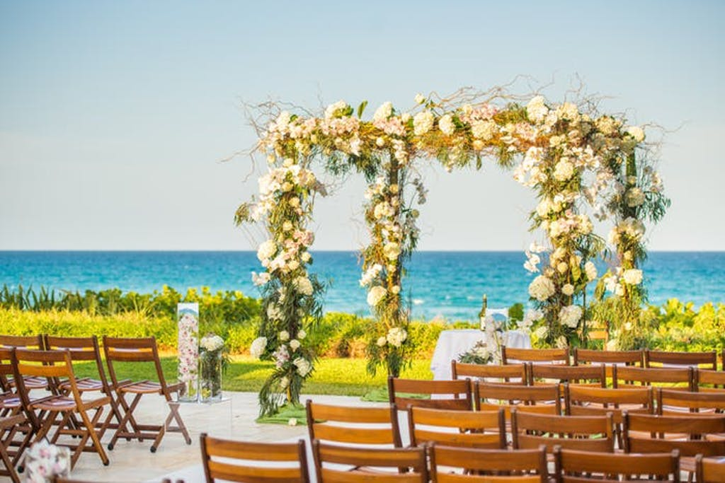 Two archways covered in green and white florals in front of bright blue water.