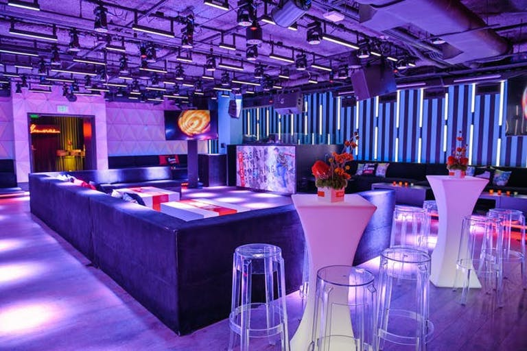Purple ceiling with purple lighting on bar and high tops.