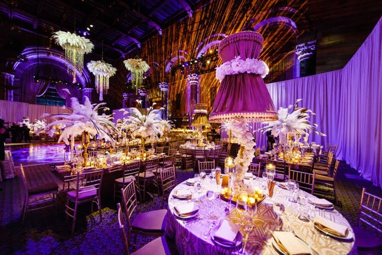a purple lit room with vintage chandeliers and decorative centerpieces