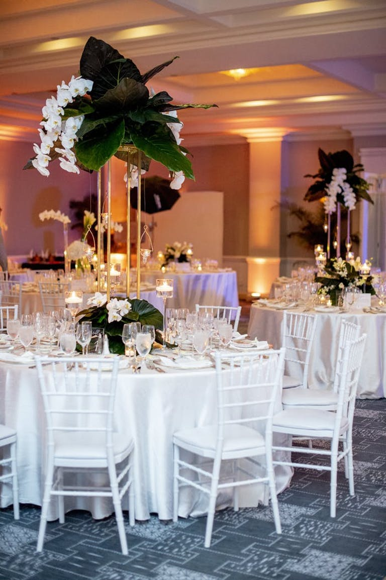 tall centerpieces with large leaves and hanging white orchids