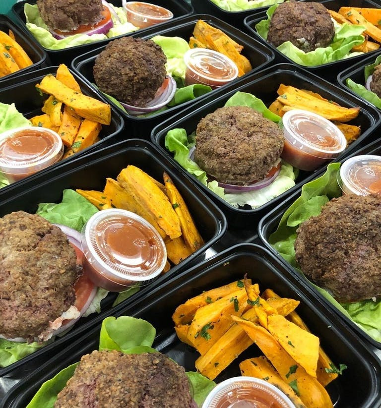 meals packed in black cartons without lids, they are all sitting next to each other