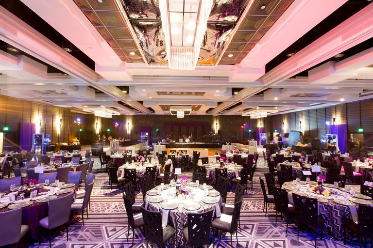 A ballroom with round tables and a pink ceiling.