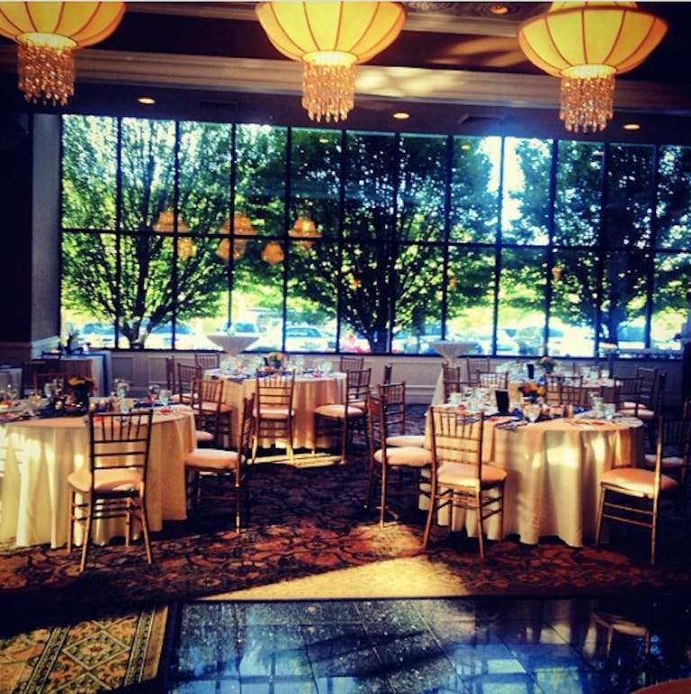 Concorde Banquets baby shower venue in Chicago with tables with white linens and wooden chairs. Large paned windows look out to greenery and trees