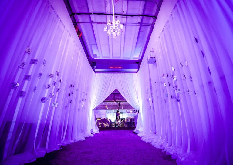 Birthday Party Entrance with Drapery and Purple Uplighting | PartySlate