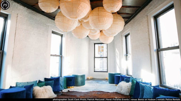 A white walled loft with Chinese lanterns on the ceiling and blue poufs on the floor