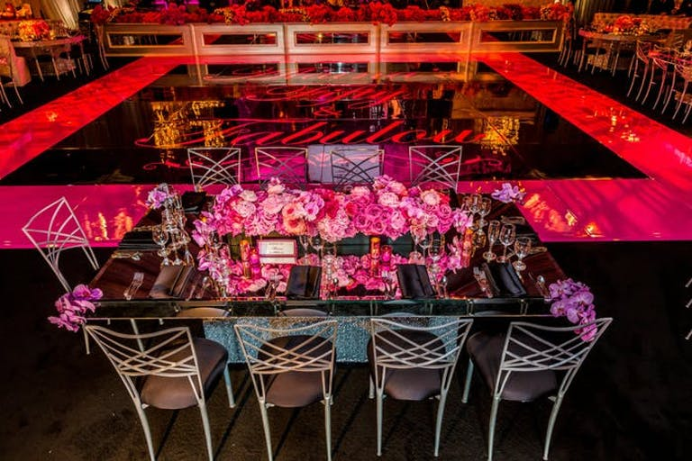 A Table with Pink Decor on the Outside of a Dance Floor with Pink Lighting | PartySlate