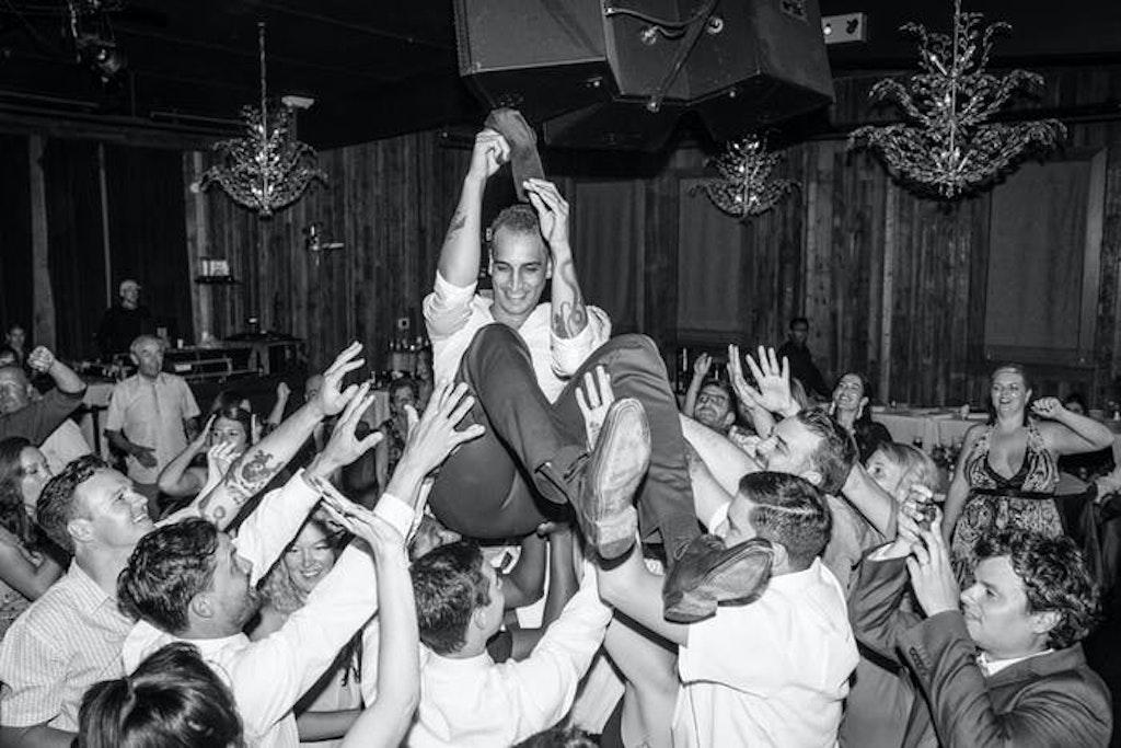 A man crowd surfs in a dimly lit ballroom