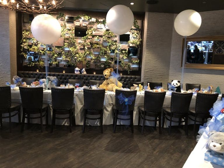 Siena Tavern baby shower venue in Chicago with long rectangular table with three white balloons anchored by stuffed animals