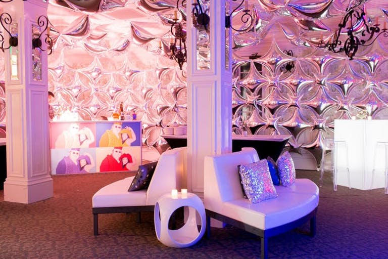 50th Birthday Party With Reflective Wall as a Backdrop with Modern White Couches Back to Back and Pink and Purple Lighting | PartySlate