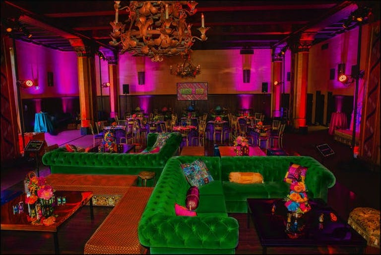 A space that is washed in a coat of pink lighting with a chandelier and green retro couches underneath