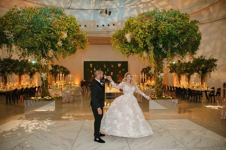a couple walks through their reception room hand in hand. The room is filled with green trees and warm lighting