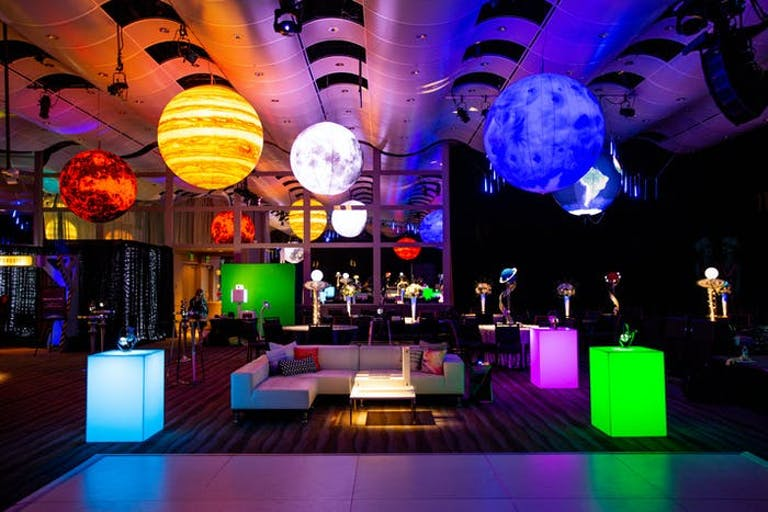 Corporate Event Space-Themed Party With Giant Planetary Décor Ceiling Installation and Rectangular LED Cocktail Tables | PartySlate