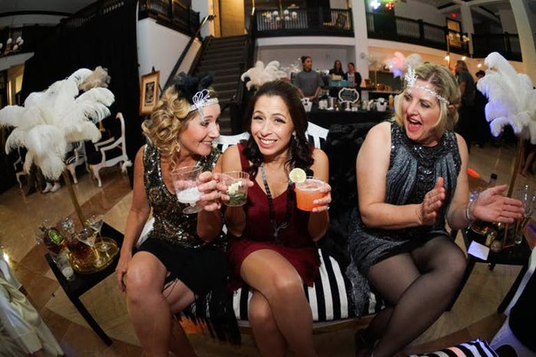 Three Women Sit on a Couch with 20s Themed Outfits and Flanked by Feathery Décor | PartySlate
