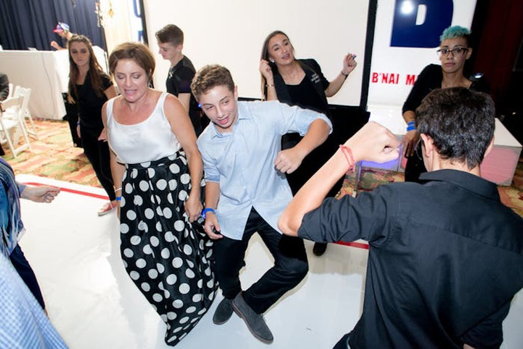 A mom and son dance together on an all white dance floor. Party guests are dancing around them