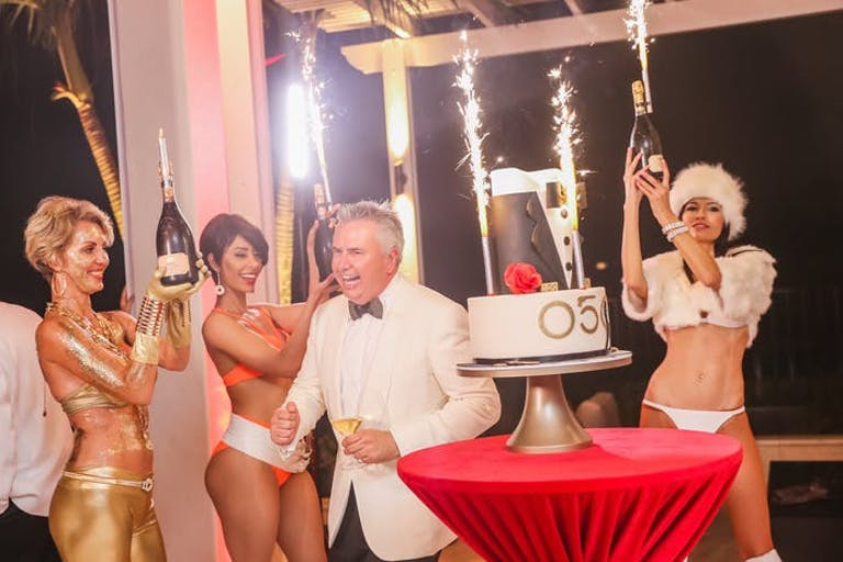 A Man in a White Tux Stands Next to a Cake and Women in Bikinis Surround Him with Bottles | PartySlate