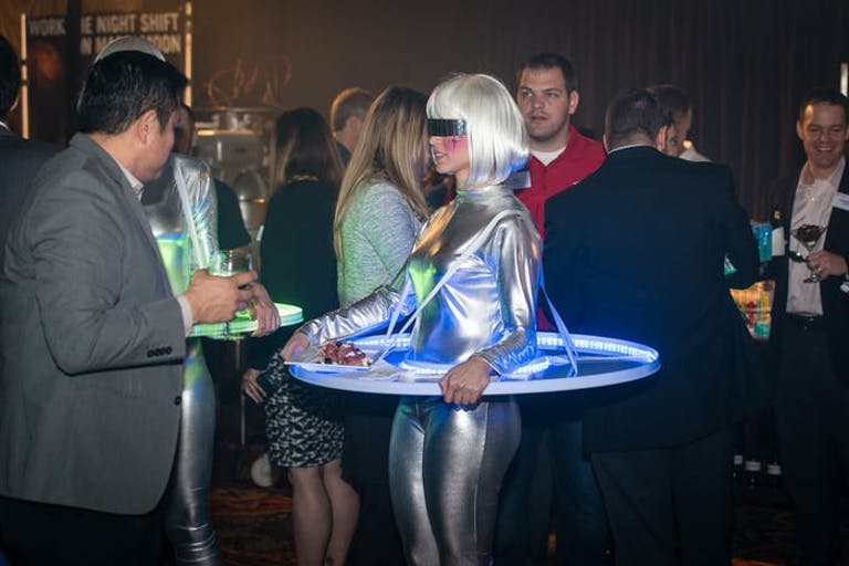 Futuristic Party With Woman in a Platinum Blonde Wig With a Silver Space Uniform and Tray Surrounding Her | PartySlate