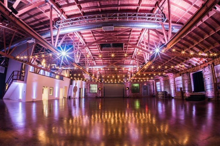 A massive warehouse with a vaulted ceiling and pink and purple lighting everywhere