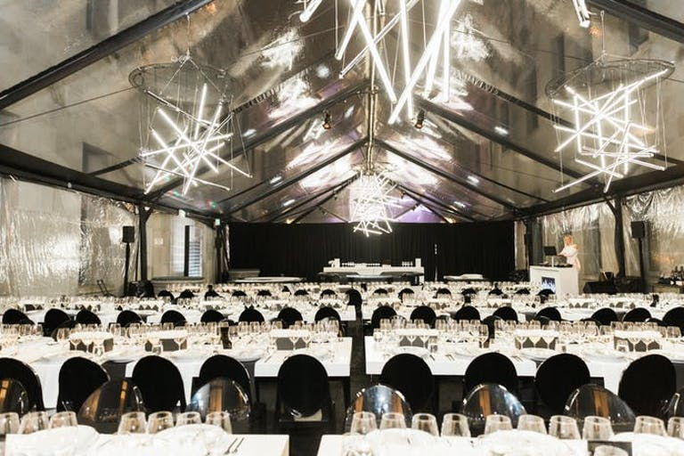 Casino-Themed Futuristic Party in Tent With White Linen, Black Chairs, and Geometric Neon Chandeliers | PartySlate