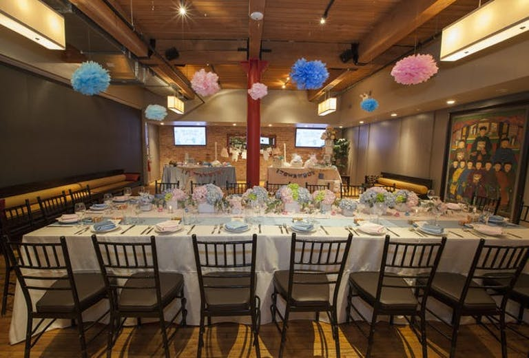 Sunda New Asian baby shower venue in Chicago with long tables with white linens and black chairs. Colorful balloons are above