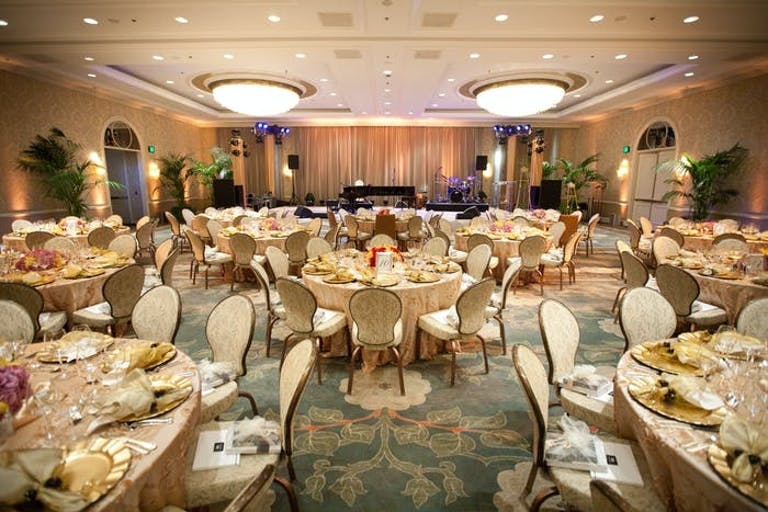 Round cream tables are in a ballroom with two lights coming from the ceiling next to recessed lighting.