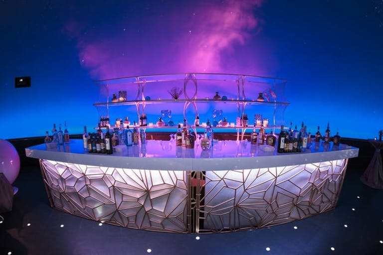 Space-Themed Party With Laser-Cut Bar Décor and Pink and Blue Uplighting | PartySlate