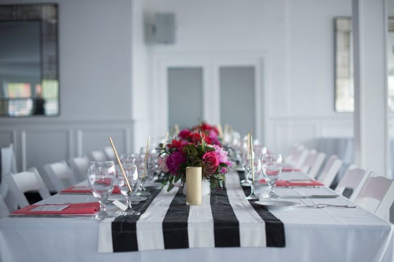White Room With Table Decked in Black and White Striped Linen and Pink Centerpieces | PartySlate