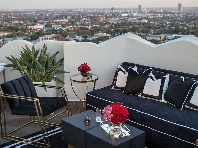 Party Lounge Area on City Rooftop With Black and White Seating and Pink Floral Centerpieces | PartySlate
