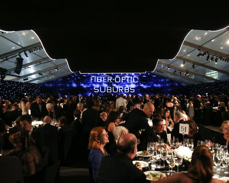 An outdoor event is flanked by two ceilings that don't meet in the middle. A screen is in the center of the room and people congregate