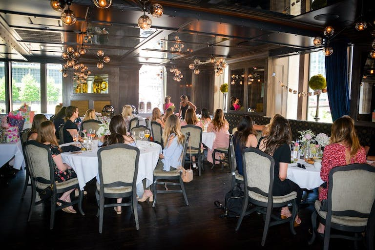 Prime and Provisions baby shower venue in Chicago with large room filled with large round tables with people and dangling chandeliers