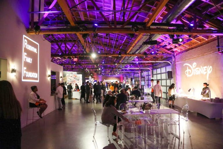 A big warehouse-like space with people walking around and graphics being shown on walls.