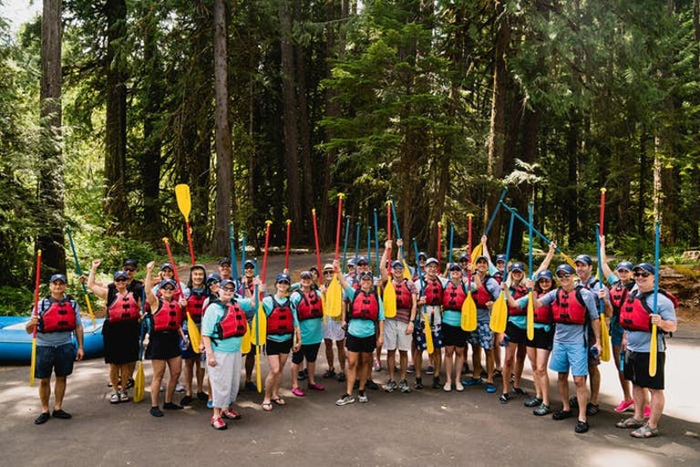 Guests at Oregon 50th Birthday Party Stand in Forest and Hold up Rowing Oars | PartySlate