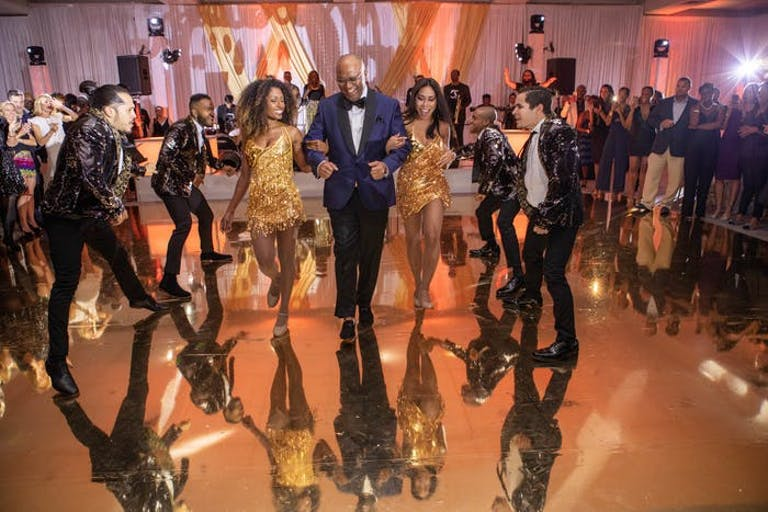 A Couple Walks Through the Dance Floor with Dancers Surrounding Them | PartySlate