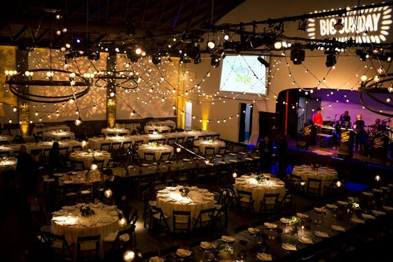 A dimly lit room with fairy lights and a monitor. Centerpieces act as spotlights