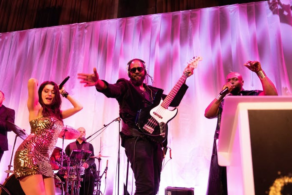 A man stands with one arm reached out to the audience and the other on an electric guitar. A lady in a gold tight dress dances to the left. A pink wavy backdrop is behind them