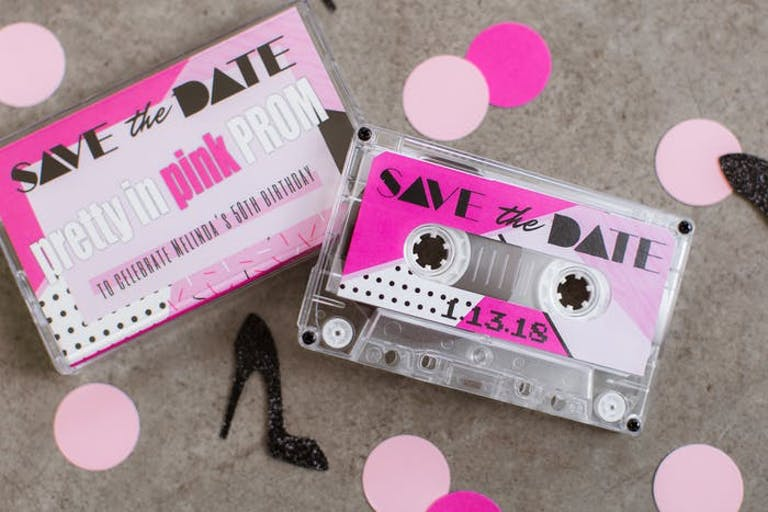 Two Cassette Tapes with Pink 'Save the Date' Printed on Them and Pink Confetti Surrounding | PartySlate