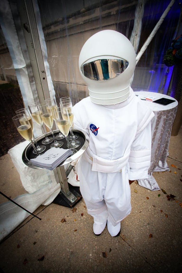 Space-Themed Party With Person in a Space Costume Holding a Tray of Champagne