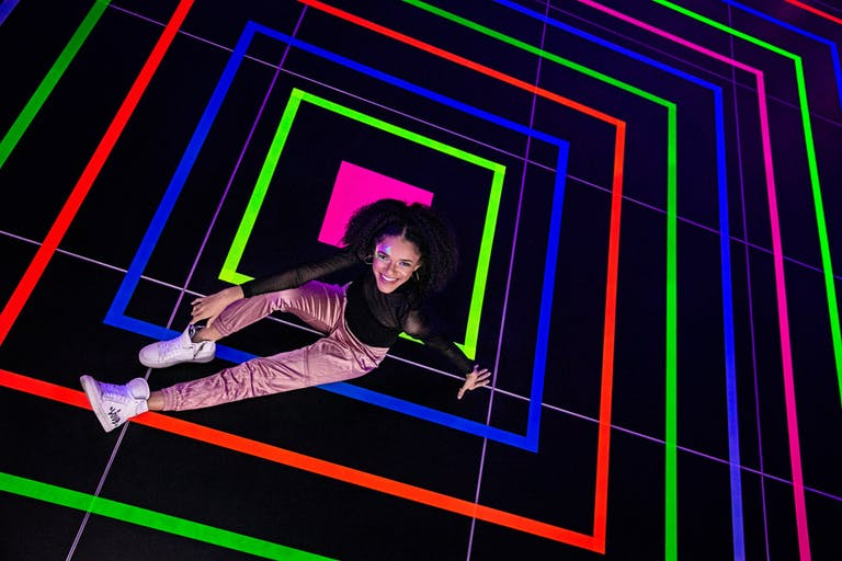 Girl Sits in Middle of Colorful Neon Square Dance Floor   PartySlate