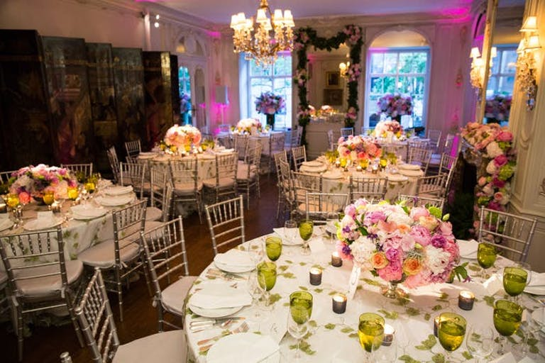 An open room with pink walls and large round tables with white linens and pink flower arrangements