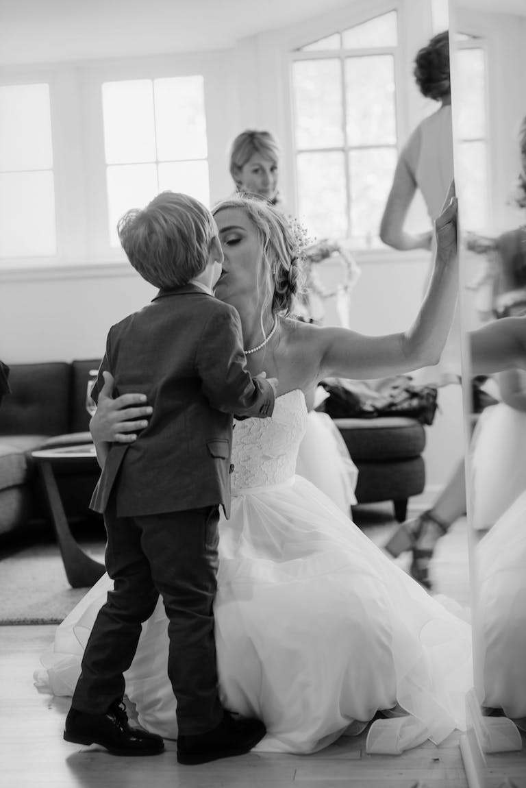 Black and white photo of bride in white wedding dress kissing young son who is wearing a tux.