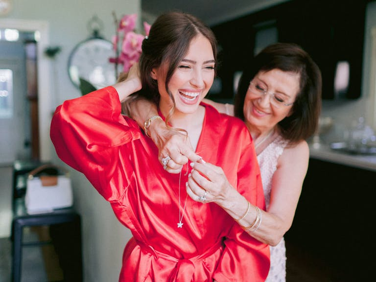 A bride in a coral-colored robe laughs as her mother stands behind her and helps clasp her necklace.