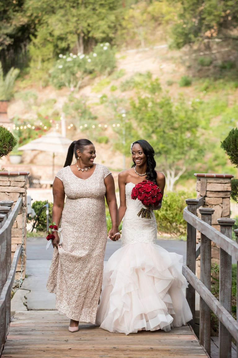 Mother walks bride holding a red-rose bouquet down the aisle.