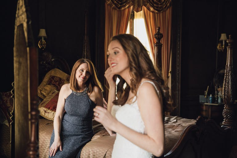 Mom sits on bed and watches daughter put on earrings before wedding ceremony.