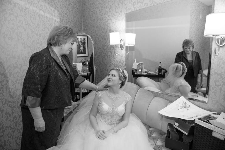 A bride sits in a dressing room and looks lovingly up at her mother who touches her on the shoulder.