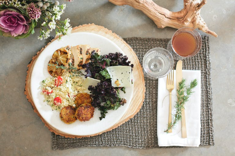 A white plate of artfully catered food rests on a circular wooden placemat atop a gray woven square placemat. White blooms and a driftwood branch accompany a glass of water, a glass of cider, and a white napkin with gold utensils and a sprig of greenery.