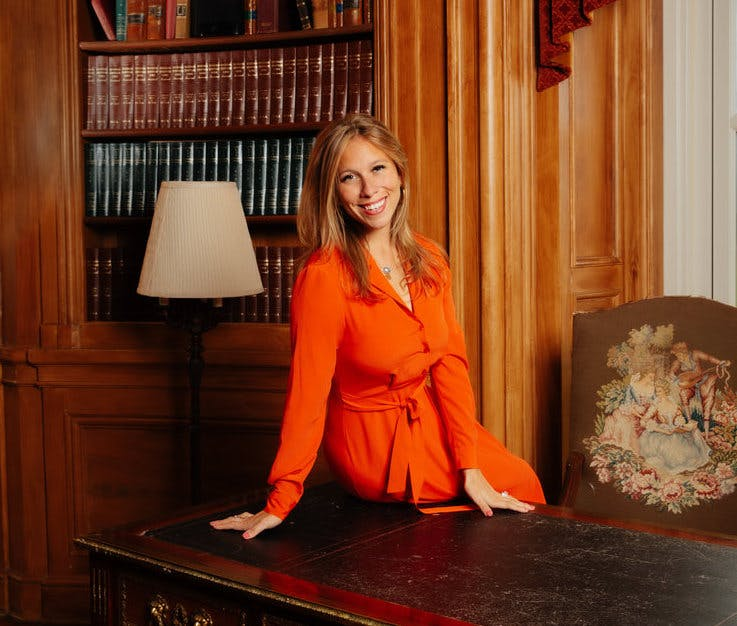Lauren Grech in a red dress sitting on a wooden desk and a book case behind her.