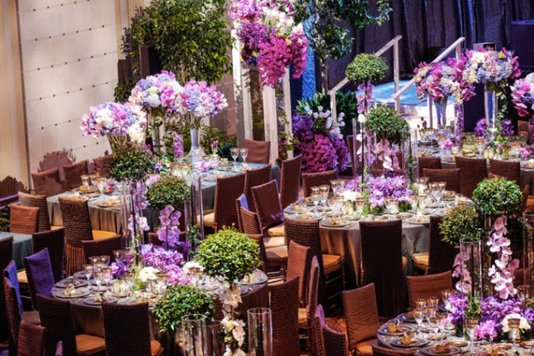 A room filled with purple and green florals on each round table