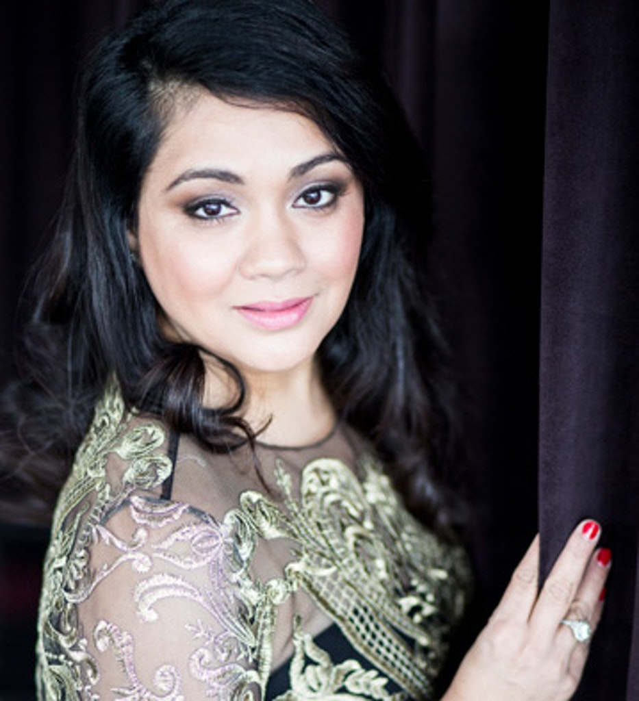 A headshot of Sonal J Shah. A black background and she stands with her hand on the wall in front of her.