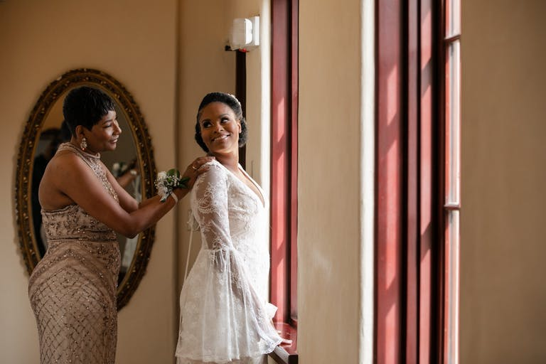 A mother helps her daughter put on her wedding dress.